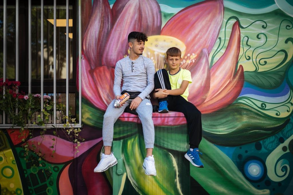 David und Julian vor einem Blumenmotiv der neuen Außenfassade des Jugendzentrums Fzwei.