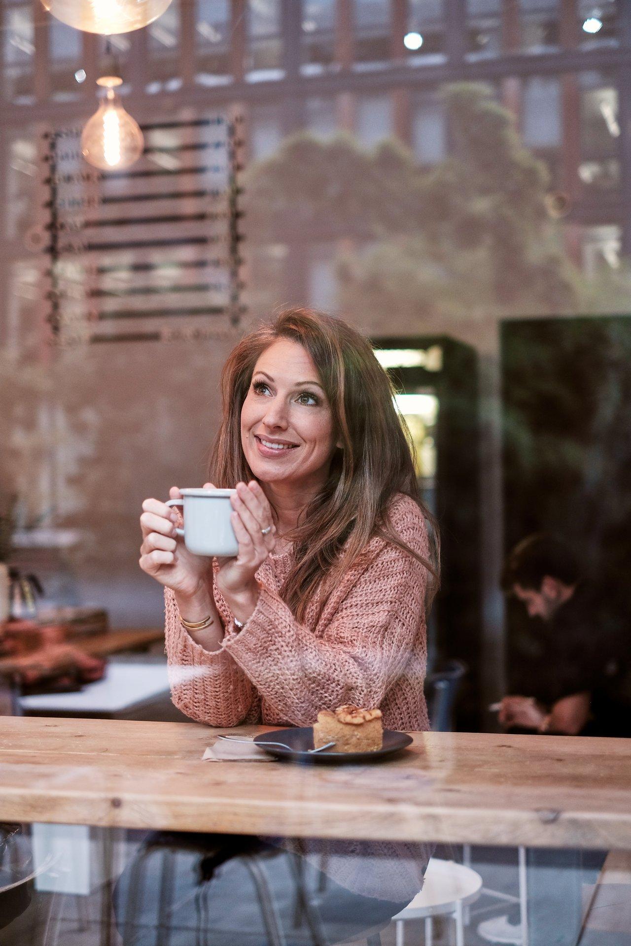 TV-Moderatorin Mara Bergmann blickt versonnen aus einem Café in den Kölner Himmel.